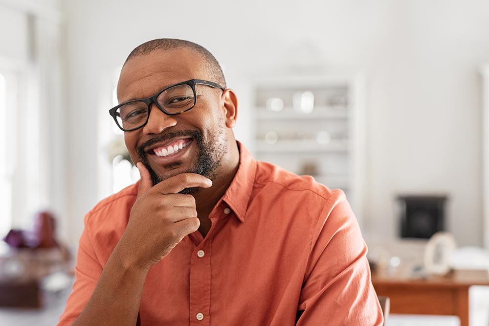 Man in orange shirt and brown glasses smiling and thinking