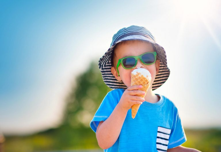 Young boy in hat outside wearing sunglasses and eating an ice cream cone